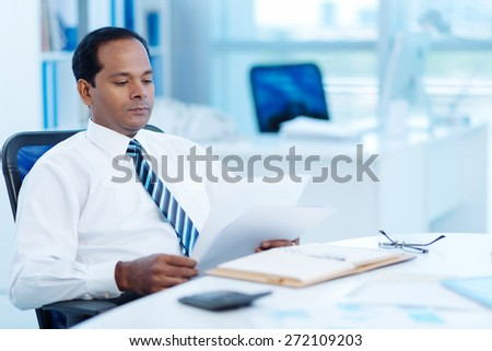 Indian entrepreneur reading business document at his workplace