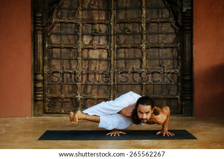 Indian ethnicity young man wit a strong body showing difficult yoga pose (Eight Angle Pose - Astavakrasana) in front of old oriental style door.