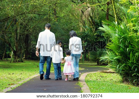 Indian family at outdoor. Rear view of parents and children walking on garden path. Exploring nature, leisure lifestyle. - stock photo