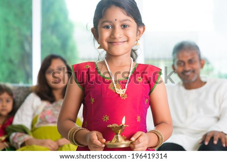 Indian family celebrate diwali or deepavali at home, little girl with traditional clothing sari, hands holding oil lamp indoor.