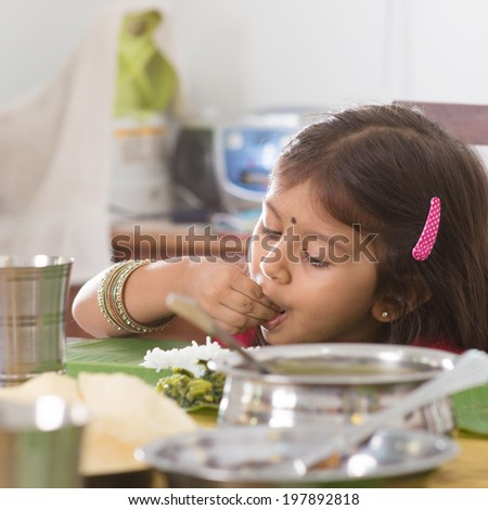 Indian family dining at home. Candid photo of Asian child self feeding rice with hand. India culture. - stock photo