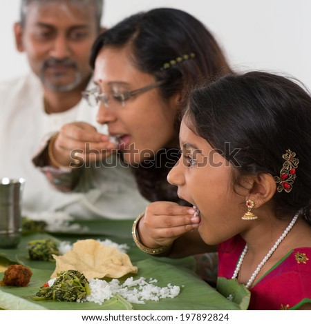 Indian family dining at home. Candid photo of Asian people eating rice with hands. India culture. - stock photo