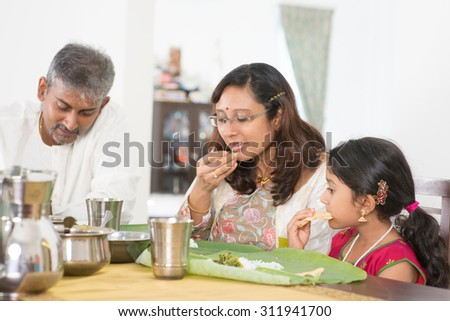 Indian family dining at home. Candid photo of India people eating rice with hands. Asian culture. - stock photo