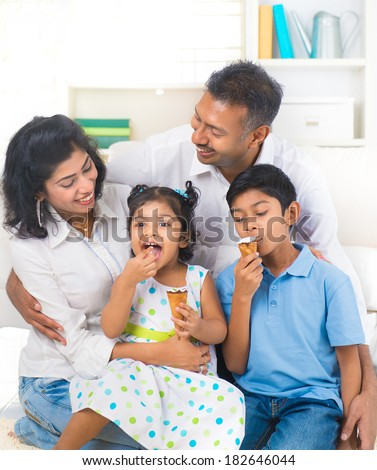 indian family enjoying eating ice cream indoor - stock photo