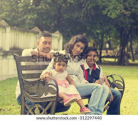 indian family enjoying quality time at outdoor park - stock photo