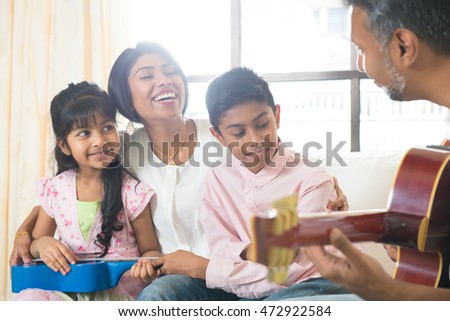 indian family enjoying quality time playing music at house