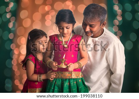 indian family fagther and daughter celebrating diwali ,fesitval of lights inside a temple - stock photo