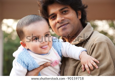Indian family, father holding the daughter in his lap - stock photo