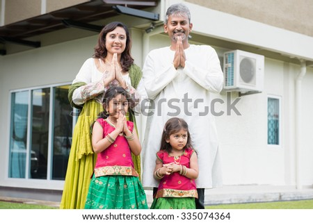 Indian family folded hands representing traditional Indian greeting on Diwali, festival of lights, outside their new home. - stock photo