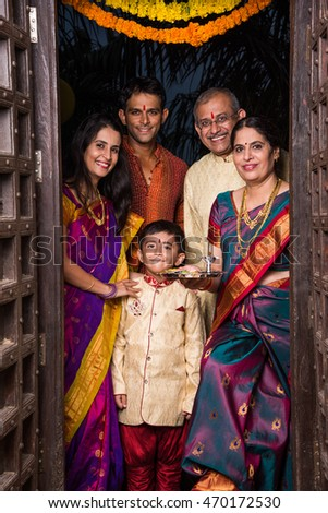 indian family group photo while entering house with puja thali at old antique door, gruha pravesh