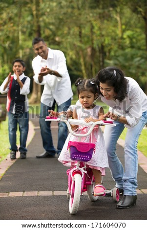 indian family guiding little daughter to cycle  - stock photo