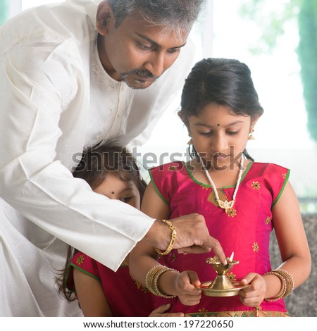 Indian family in traditional dress preparing to celebrate diwali or deepavali at home. Little girl hands holding oil lamp during festival of light. - stock photo