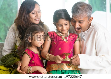 Indian family in traditional sari celebrate diwali or deepavali at home, little girl hands holding oil lamp with father indoors.