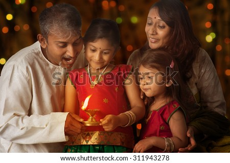 Indian family in traditional sari lighting oil lamp and celebrating Diwali, fesitval of lights inside a temple. Little girl hands holding oil lamp with beautiful bokeh background. - stock photo