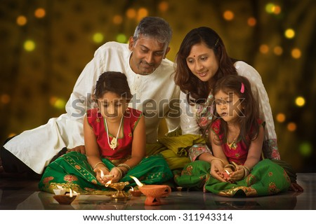Indian family in traditional sari lighting oil lamp and celebrating Diwali, fesitval of lights inside a temple. Little girl hands holding oil lamp indoors. - stock photo