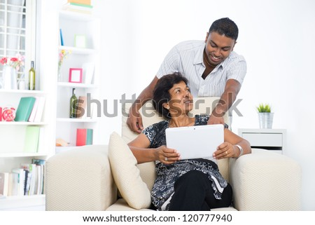 indian family lifestyle photo surfing on the Internet, son and mother - stock photo
