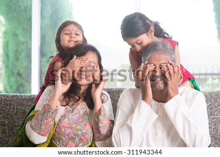 Indian family living lifestyle at home. Cute girls in traditional sari costume covering father and mother eyes. Asian parents and children. - stock photo