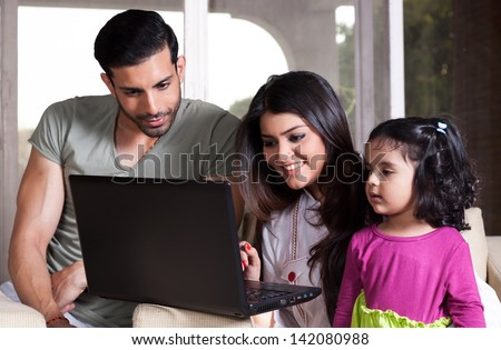 Indian family of three using laptop, young couple relaxing at home - stock photo