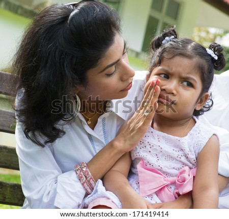 Indian family outdoor. Parent is comforting her crying child. - stock photo