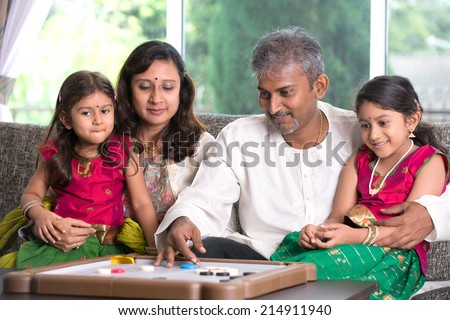 Indian family playing carrom game at home. Parents and children indoor lifestyle.
