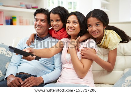 Indian Family Sitting On Sofa Watching TV Together - stock photo
