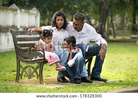 indian family sitting on the bench in the park - stock photo