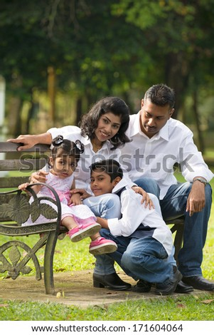 indian family sitting outdoor on the bench in the park  - stock photo