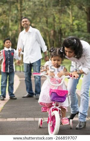 indian family teaching their kids cycling in the outdoor park
