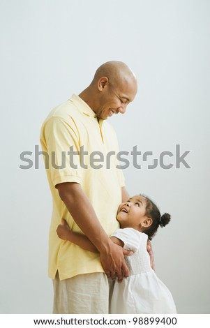 Indian father and daughter hugging - stock photo