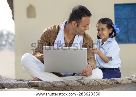 Indian father and daughter laughing over something while using laptop - stock photo