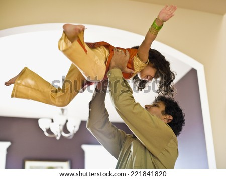 Indian father holding daughter in air - stock photo