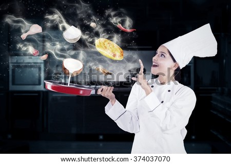 Indian female chef cooking in the kitchen with magic while wearing chef uniform - stock photo