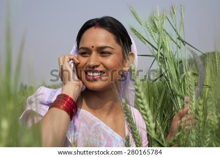 Indian female farm worker looking away while talking on mobile phone - stock photo