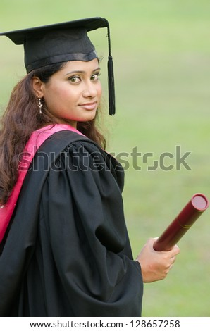 indian female graduate with green background - stock photo