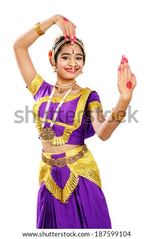Indian female performing Bharathanatyam doing the action of adorning oneself in violet color costumes   - stock photo