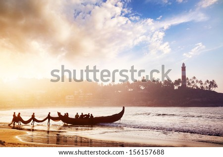 Indian fishermen in silhouette with fishing nets near the boat on the beach in the morning at lighthouse background in Kovalam, Kerala, India   - stock photo