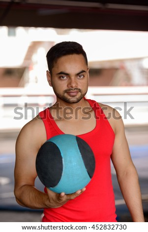 Indian fitness man holding exercise ball