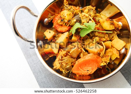 indian food spicy mixed vegetable curry over modern stripped tablecloth background