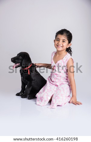 indian girl and black labrador puppy, asian girl with dog - stock photo