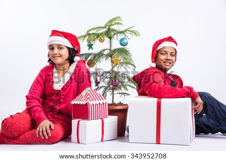 Indian girl and indian boy in red cloths and red santa hat, sitting and smiling with gift boxes and christmas three, indian kids and christmas celebration, asian kids and christmas, Indian christian - stock photo