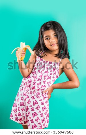 indian girl eating banana, 4 year old asian girl eating banana, girl with banana, little girl or small girl eating banana, isolated on green background - stock photo