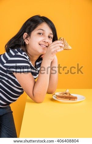 indian girl eating sandwich, asian girl and sandwich, cute indian girl posing with sandwich on yellow background - stock photo