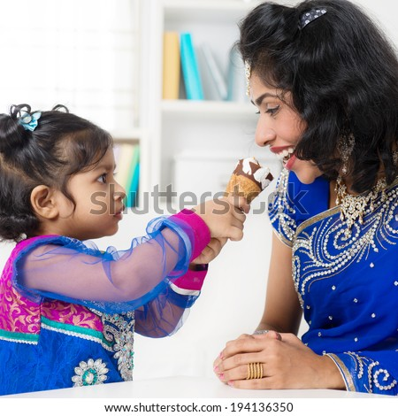 Indian girl feeding her mum ice-cream. Asian family living lifestyle at home. - stock photo