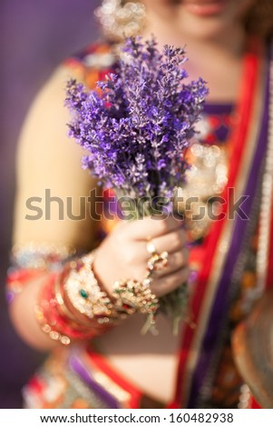 Indian girl holding lavender flowers aromatherapy and beauty spa. Indian dancer in traditional wear with bunch lavender flowers. Natural beauty concept and parfume.  - stock photo