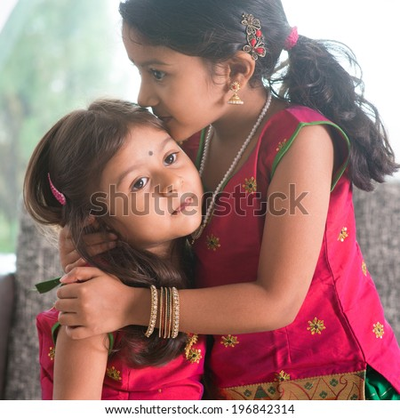 Indian girl kissing her younger sister with love. Asian family at home. Beautiful daughters in traditional India sari. - stock photo