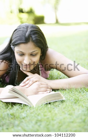 Indian girl laying down on green grass in the park, reading a book and smiling.