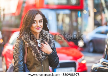 Indian girl portrait in London. She is standing by a busy road with blurred traffic on background. There are cars and red buses. She is smiling and looking at camera. Travel and lifestyle concepts