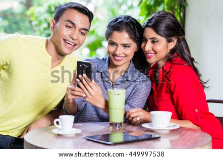Indian girl showing pictures on smart phone to her friends in an Indian cafe - stock photo