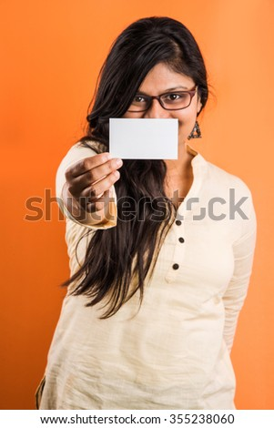Indian girl shows her business card to camera, indian woman holding a blank card, joyful young businesswoman holding a business card and laughing isolated on orange, Confident woman with business card - stock photo
