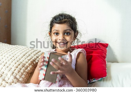 Indian girl so happy to have a present - stock photo